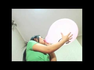 Asian woman pink smiley balloon blow to pop from below