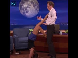 Нина Добрев на шоу просит ведущего Конана ОБрайена помочь ей показать позу Скорпиона из йоги и побыть минуточку стеной.