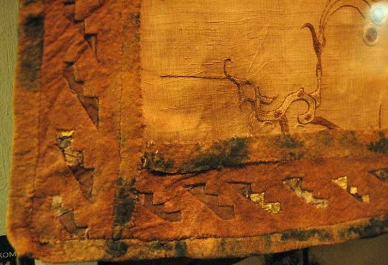 Шелковая китайская ткань, вышитая цепным стежком и вшитая в седло, найдена в кургане 5 в Пазырыке в горах Алтая (современный Казахстан), датируется 300 или 200 годами до нашей эры. (РУБИНСОН, Карен С. (1990). 'Текстиль из Пазырыка. Исследование переноса и трансформации художественных мотивов, Экспедиция, Том 32, 1, с. 49-61) https://alexandramakin.com/2020/10/01/early-medieval-mostly-textiles-4/