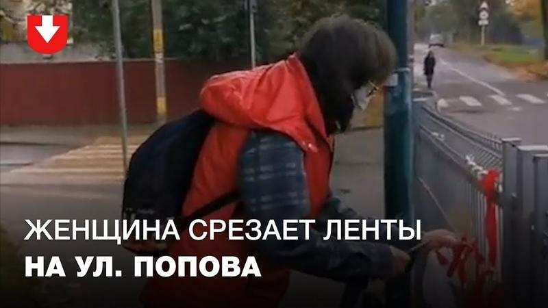 Люди спорят с женщиной которая срезает ножом бело красно белые ленты на ул Попова в Минске